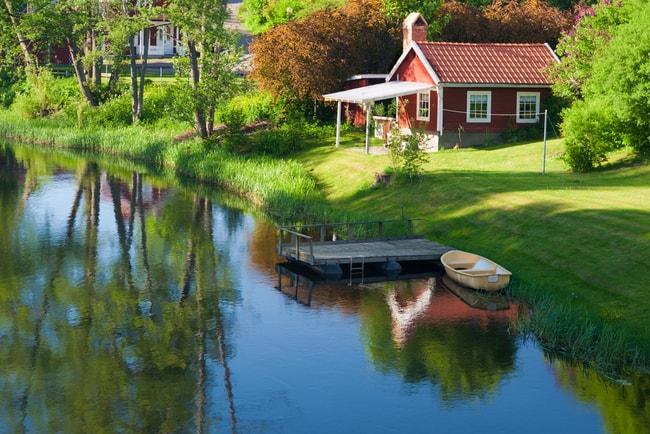 sommarstuga vid sjö med roddbåt vid brygga