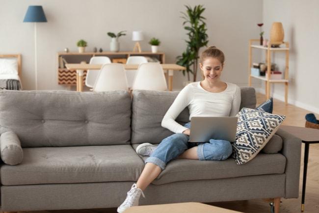 leende ung kvinna med laptop i soffa i sin lägenhet