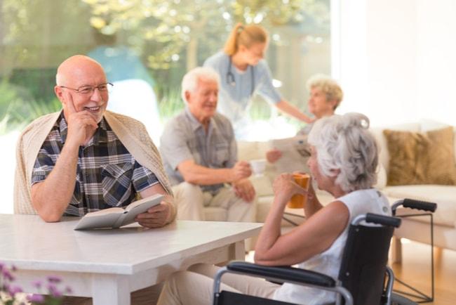 äldre man och kvinna vid bort i matsal på ett vårdboende