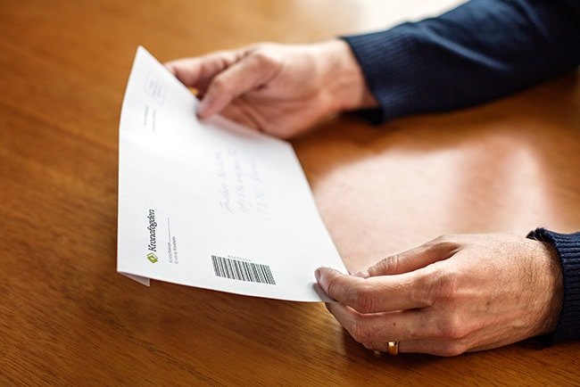 händer håller i ett brev från Kronofogden