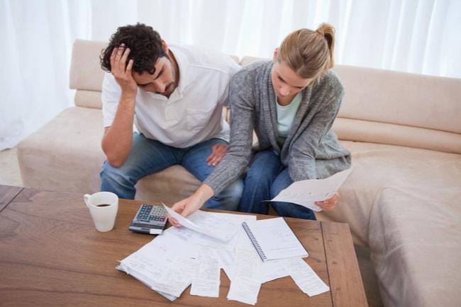 konfunderat ungt par med kvitton och miniräknare i vardagsrum