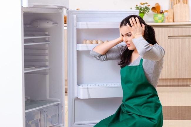 orolig kvinna vid tömt öppet kylskåp