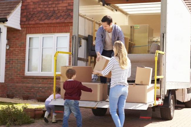 barnfamilj lastar ur flyttkartonger ur flyttbil