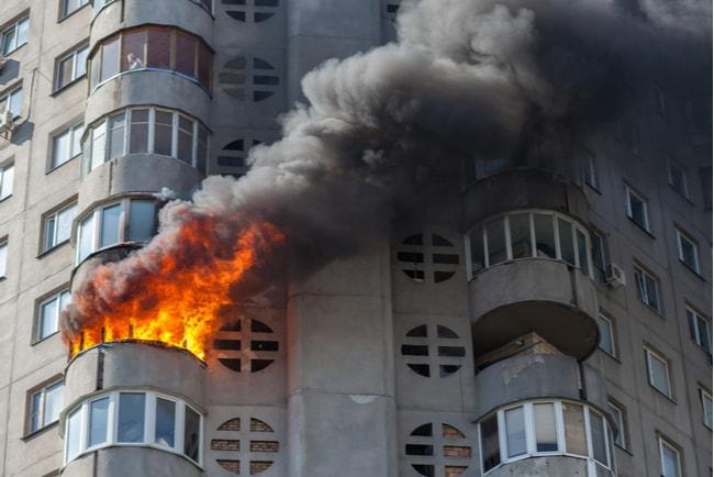 eld och rök från ett fönster i högt lägenhetshus