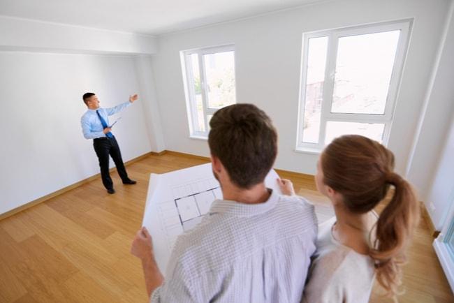 mäklare visar fönster i tom lägenhet för ungt par med planritning i händerna