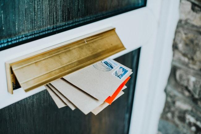 en bunt brev sticker ut ur brevinkast på dörr