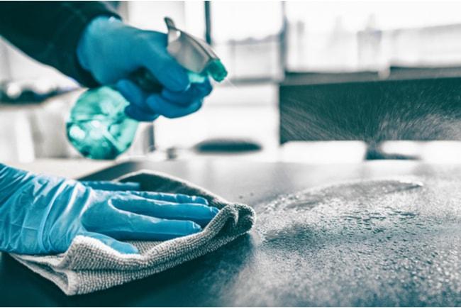 händer med handskar sprayar vatten på bord och torkar med trasa