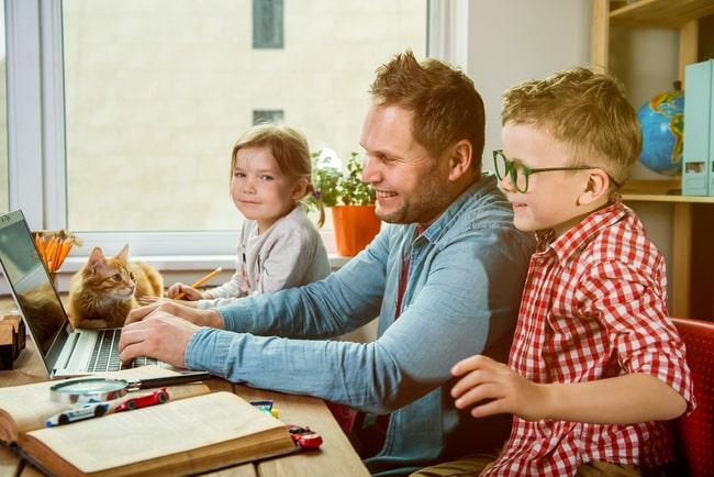 en pappa och två barn vid skrivbord framför laptop