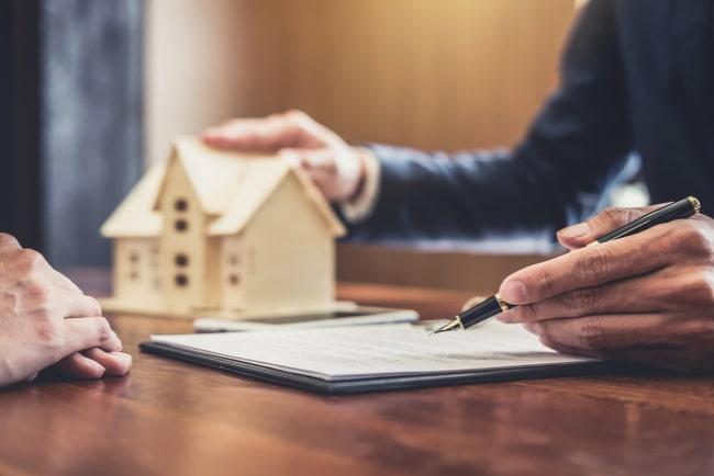 fastighetsmäklare med hand på husprototyp