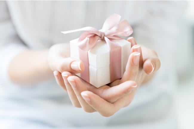 kvinnas händer räcker fram ett litet paket med rosa band runt