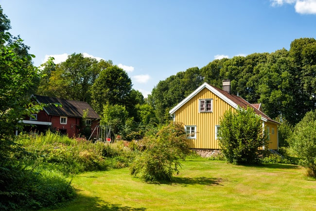 gul villa med grönskande tomt och träd omkring
