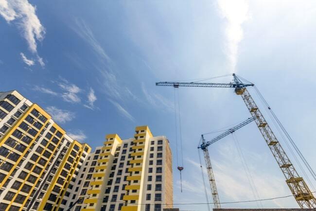 Lyftkran vid bygge av gula höga flerfamiljshus.