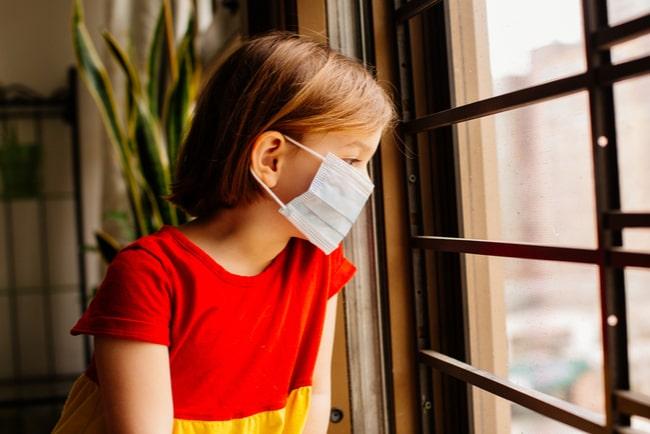 liten flicka med munskydd tittar ut genom fönster