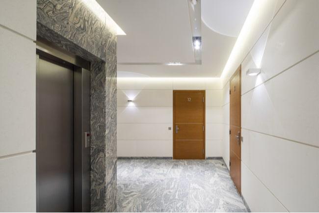 trapphusutrymme med två lägenhetsdörrar och en hiss