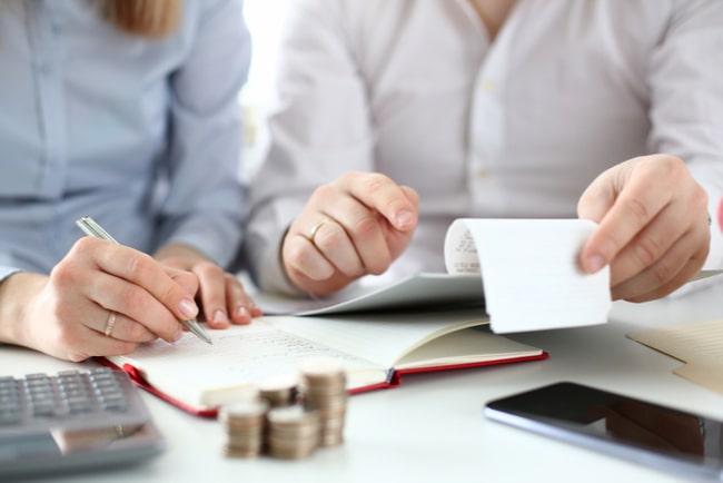 kvinna och man antecknar i block med mynt och miniräknare omkring sig