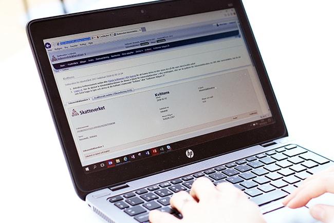 Händer som skriver på en laptops tangentbord på skatteverkets hemsida
