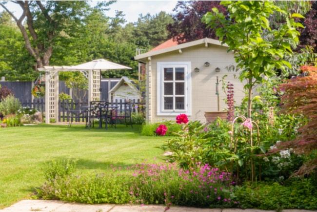 litet fritidshus i grönskande engelsk trädgård