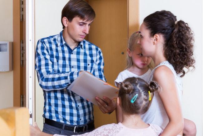sträng hyresvärd visar papper för hyresgäst med två barn