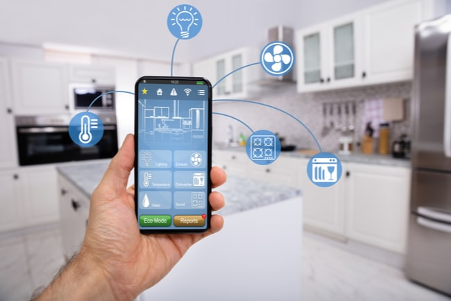 hand håller upp mobil med ikoner för styrning av det smarta hemmet