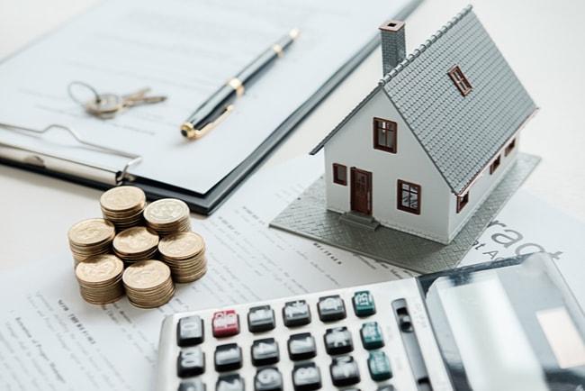 husmodell med mynt, papper, nycklar och miniräknare runt omkring