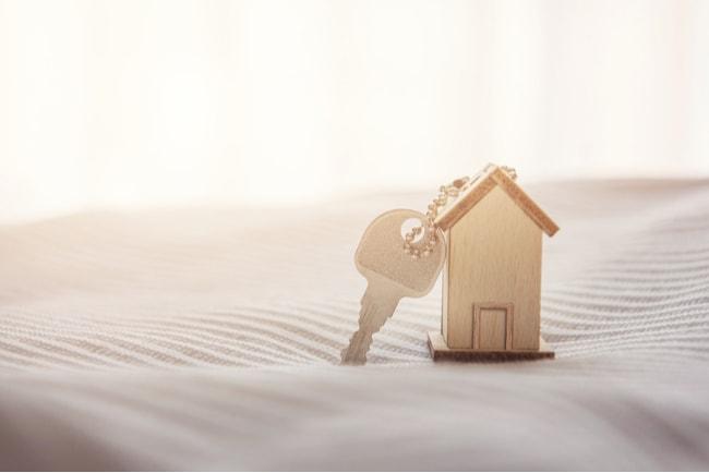 husnyckel med miniatyrhus i trä på en säng
