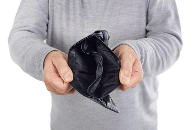 Man med grå stickad tröja håller upp en svart plånbok som är tom.