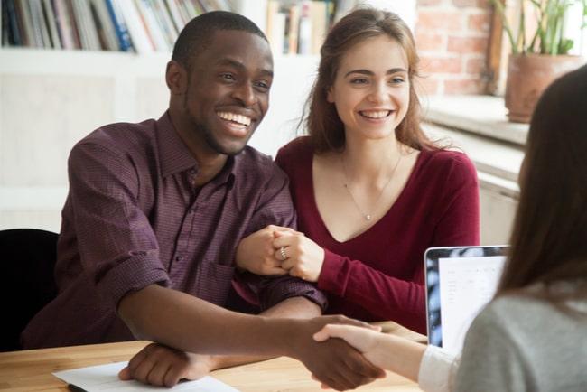 ungt leende par skakar hand med en bankman