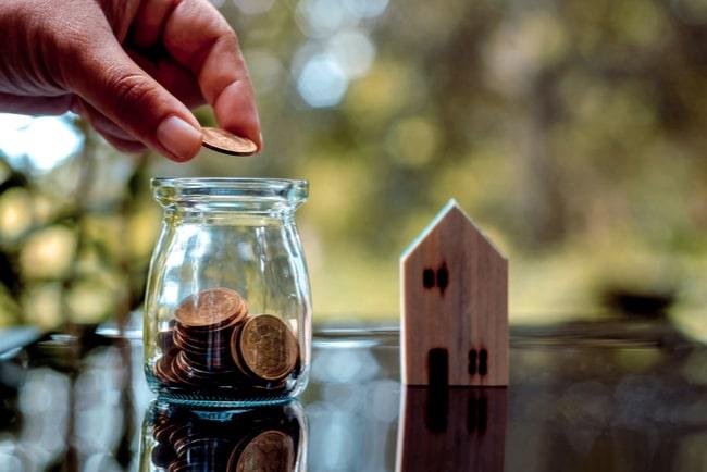 hand lägger mynt i burk miniatyrhus i bakgrunden