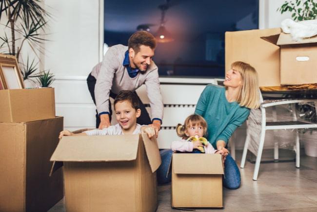man, kvinna och två barn leker med flyttkartonger