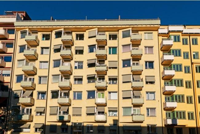 Fasadbild av flerbostads hur i olika nyanser av gult.