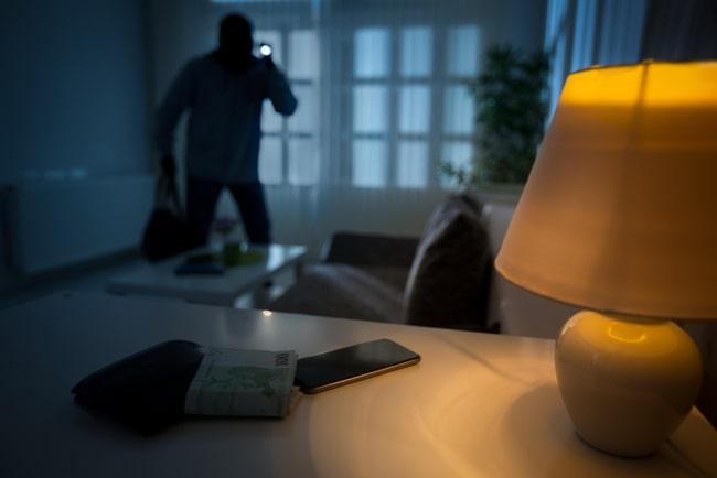 Tjuv gör inbrott i hem där lampan lyser och mobiltelefonen och pengar ligger på bordet.