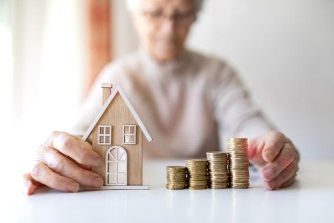 äldre kvinna håller i miniatyrhus och högar av mynt