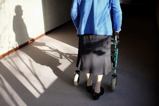 äldre kvinna går med rollator i korridor
