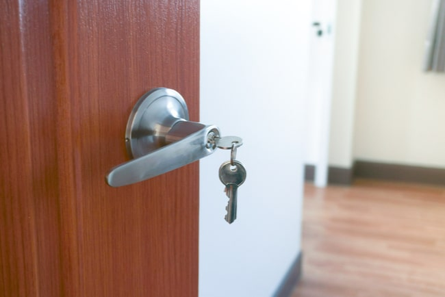 närbild på dörrhandtag med nyckel på öppen dörr in till ett rum