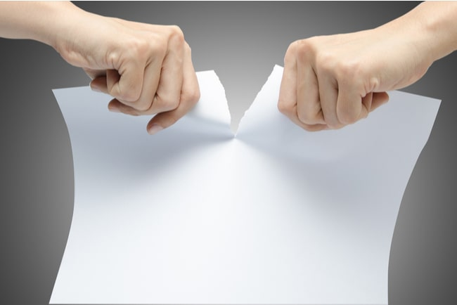 händer river vitt papper mitt itu