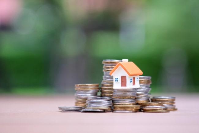 minihus står på mynt som symbol för bostadsmarknaden