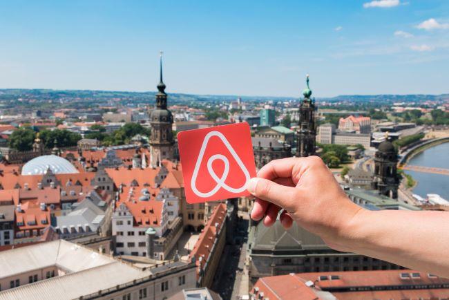 hand håller airbnb:s logotyp framför utsikt över staden Dresden i Tyskland