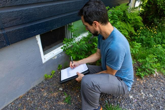 man med anteckningsblock inspekterar en husgrund