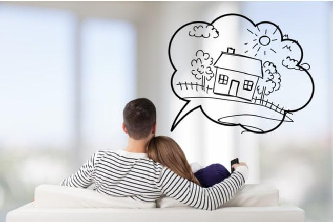 ungt par sitter i soffan och drömmer om bostad