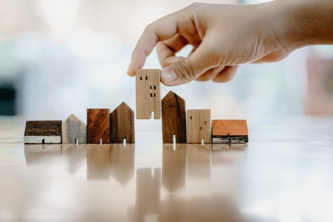 hand flyttar på ett av flera miniatyrhus i trä från en rad