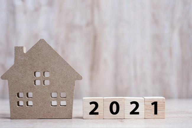 miniatyrhus bredvid träklossar med siffrorna 2021