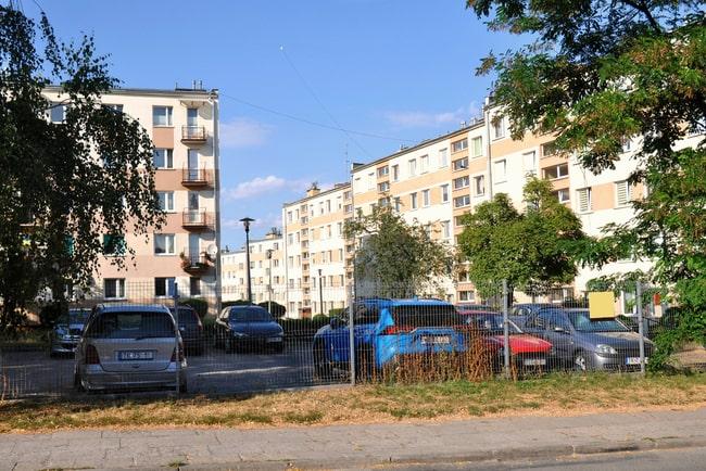 bilar på parkeringsplats framför lägenhetshus