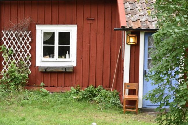 fönster och dörr på ett rött litet fritidshus