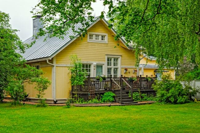 gul villa med trädgård på baksidan