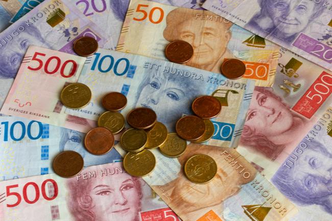 Svenska sedlar och mynt i olika valörer.