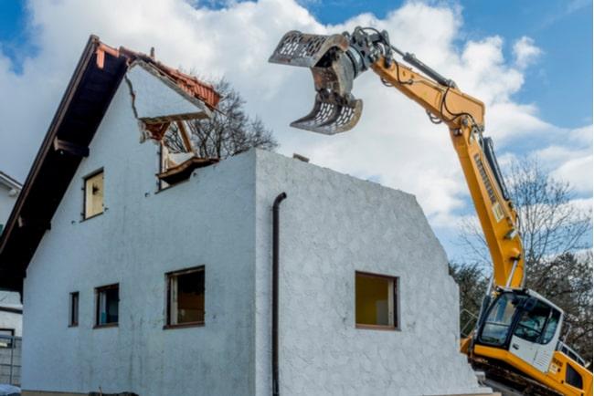 grävmaskin river ett vitt hus