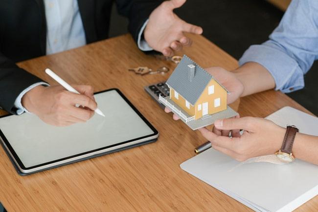 mäklare och köpare förhandlar över en miniatyrvilla