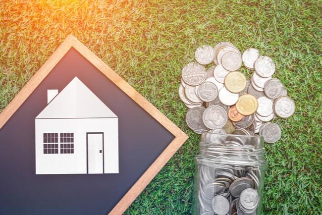pappersutklipp av ett hus ligger på griffeltavla bredvid en glasburk med mynt