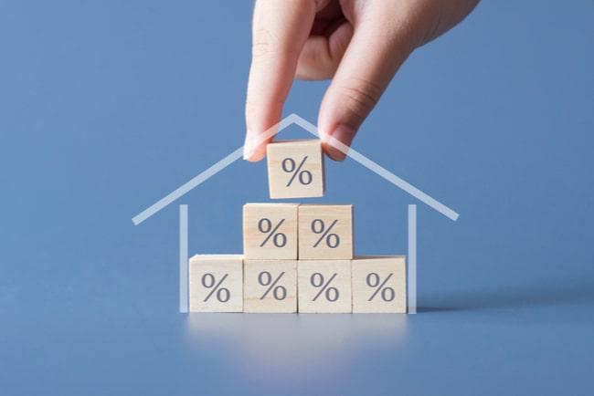 hand bygger med klossar med procenttecken inom konturerna av ett hus