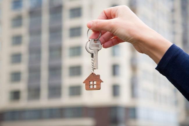 hand håller upp nyckel bostadsrättshus i blurrad bakgrund